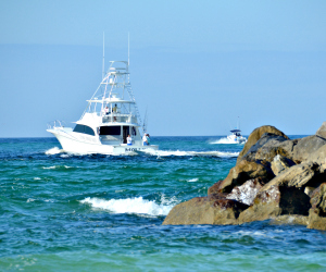 Fishing boat heading out through the East Pass in Destin to the Gulf of Mexico.